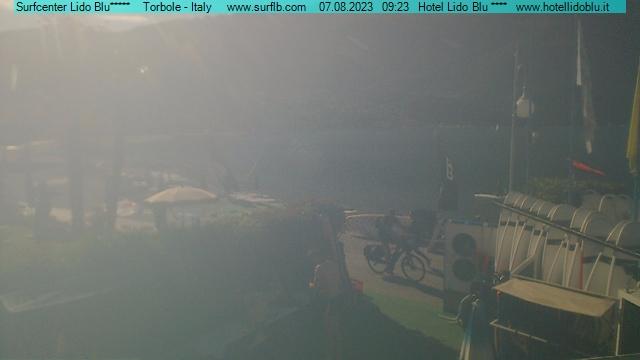Die Webcam blickt von der Surfschule am Hotel Lido Blu über den Strand von Torbole Richtung Hafen.